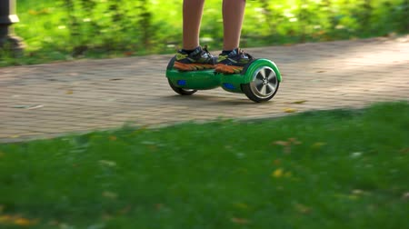 self balancing : Ukraine, Kiev 17.09.2017. Riding green gyroscooter in the park. Boys legs on gyroscooter, close up.