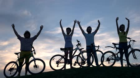 unutulmayan : Group of young cheerful cyclists at sunset. Four young friends with bicycles waving with hands on sky background. Unforgettable summer trip.