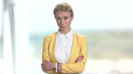 сложены : Sad mature business woman. Portrait of frustrated lady in yellow suit. Bright blurred office background.