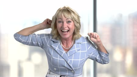 директор : Portrait of happy middle-aged business woman in office rejoicing success. Emotional screaming entrepreneur rejoicing in victory. Bright blurred background.