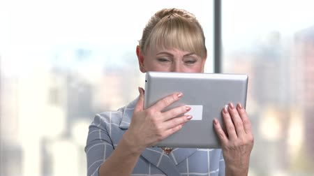 attorney : Happy senior woman with tablet in office. Elegant smiling middle aged businesswoman with tablet computer.