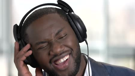 listens : Black man in suit listening to music with headphones. Close up face. Bright blurred windows background.