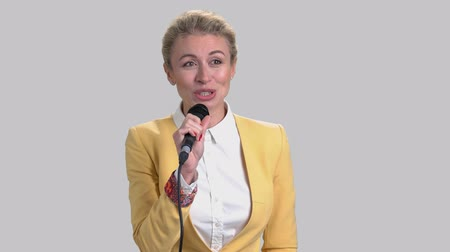 вести : Business conference speech. Female conference speaker isolated on grey background. Стоковые видеозаписи