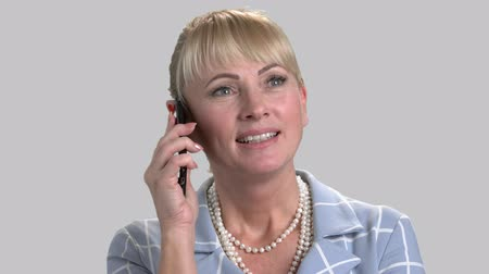 backround : Businesswoman talking on phone. Caucasian middle aged lady on grey background.