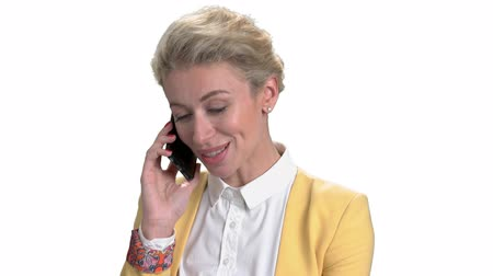 backround : Portrait of mature businesswoman talking on phone. Lady in yellow office jacket talking by phone. White isolated background.