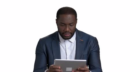 darkskinned : Black man in suit playing games in tablet. Enthusiastic young manager with emotional interest holds computer tablet against white isolated background. Stock Footage