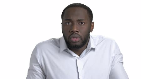 bewilderment : Sequence of different emotions by young black man in white shirt. Pensive, surprised, wondered and puzzled emotions. White isolated background. Stock Footage