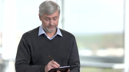 panoya : Man with clipboard working and taking notes. Portrait of mature caucasian man writes down notes standing in bright office against windows. Stok Video