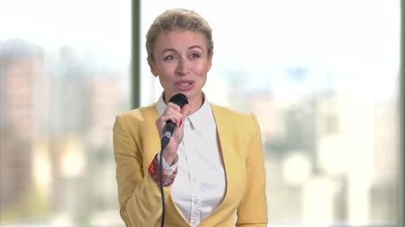 voz : Business woman speech indoor. Female conference speaker in yellow suit against blurred window background.