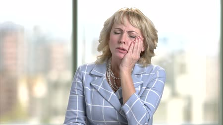 backround : Middle aged businesswoman with terrible toothache. Worried woman in suit feels strong pain in her teeth against blurred windows background. Stock Footage