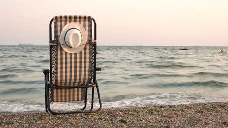 připevnění : Hat attached to chaise lounge chair on beach. Seashore and sunset concept.