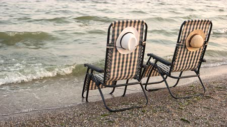 urlop : Checkered deck chairs on the sandy beach. Romantic summer vacation on seashore.