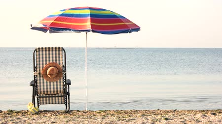chaise longue : Tranquil morning sea and sunbath attributes. Back view chaise-longue and beach accessories near the sea. Stock Footage