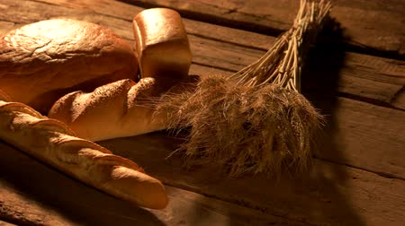 baker : Homemade bread on rustic wooden background. Fresh bread, baguettes and bundle of wheat ears on rustic wooden table. Wheat bread diet.