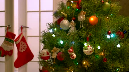 stockings : Christmas tree decorated with balls and angels. Lights twinkling on green New Year tree. Merry Christmas background. Stock Footage