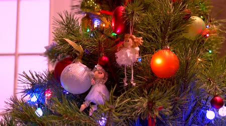 adorno : Christmas tree with garlands and toys. Beautiful angels and baubles hanging on New Year tree close up. New Year tree festive decor.