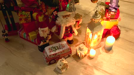santaclaus : Gift boxes and Christmas decorations. Santa Claus toy, boxes with presents, lantern, gingerbread house and candles on wooden background. Merry Christmas and happy New Year.