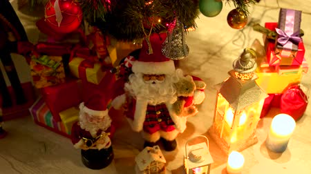 enfeite de natal : Christmas gifts and lights under Christmas tree. New Year tree with presents and decorations. Winter holiday concept.