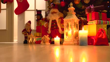 santaclaus : Burning candles and Christmas decorations. Lantern with a burning candle, Santa Claus toy, gift boxes and Christmas tree. Christmas holiday traditions. Stock Footage