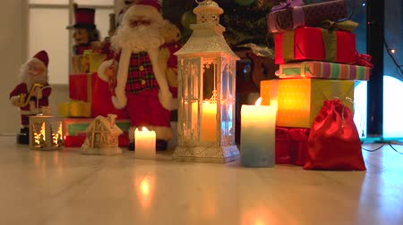 santaclaus : Christmas holiday gifts and ornaments under tree. Burning lantern, candles, gift boxes and decorations on wooden floor. Festive holiday atmosphere.