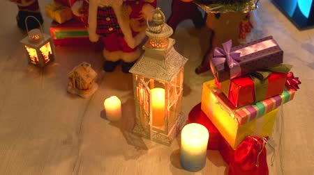 santaclaus : Gifts and candles under Christmas tree. Christmas and New Year decoration on wooden floor. Winter holiday home festive atmosphere. Stock Footage