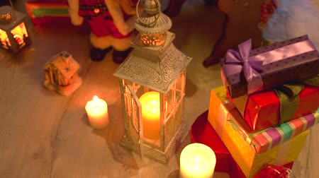 santaclaus : Christmas holiday candles and gifts. Burning lantern and Christmas decoration on wooden floor. Festive holiday scene. Stock Footage