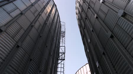 хранилище : Huge metal buildings, up view. High metal grain storage facility. Look at the sky.