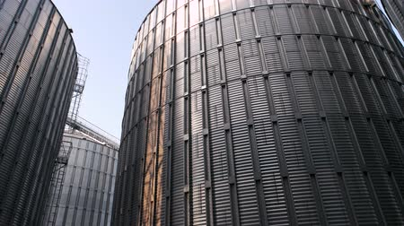 хранилище : Large grain silo for storing barley. Metal steel building, blue clear sky background.