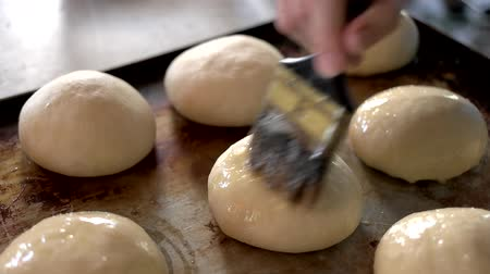 pekař : Preparation of buns at bakery. Slow motion unbaked french bread rolls getting brushed with yolks. Homemade fresh pastry.
