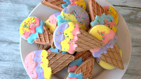 receita : Plate with ice cream cone cookies. Tasty glazed biscuits, top view. Healthy treats for kids.