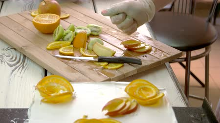 glassa : Chef hand processing apple slices with lemon juice. Assortment of cutted fruits on wooden board. Cooking cake at restaurant.