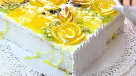 galaretka : Chef decorating cake with white cream. Cake covered with fresh fruits slices and jelly. Delicious dessert for gourmet. Wideo