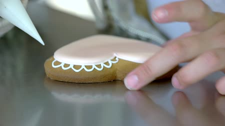kek : Female hands decorating heart-shaped cookie. Woman decorates biscuit with pink glaze. Pastry for Valentines Day.