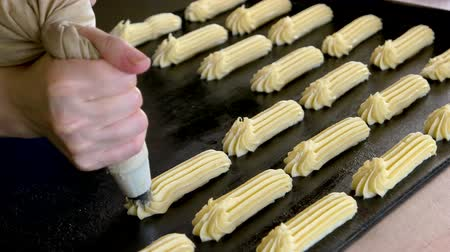 baking dishes : Pipe choux pastry onto oven tray. The dough for the eclairs extruded from a pastry bag. Production of french pastry. Stock Footage