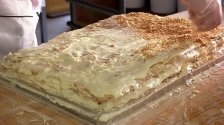 migalhas : Chef sprinkles biscuit crumbs on napoleon cake. Napoleon cake recipe. Best dessert for holiday celebration.