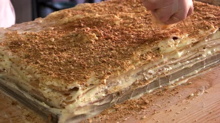 buttercream : Covering big layered dessert with crumbs. Biscuit crumbs and cream. Traditional recipe of napoleon cake. Fresh puff dough. Confectionery business concept.