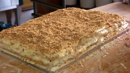 migalhas : Sprinkling cake with crumbs. Covering Napoleon cake with grinded bread. Lots of crumbled biscuits. Traditional recipe of delicious cake.