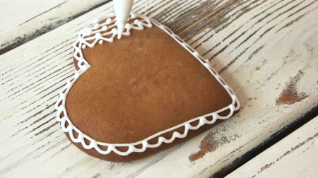 şeklinde : Piping a lace on fresh gingerbread cookie. Decoration of brown heart-shaped biscuit with text I love you. Homemade pastry for Valentines holiday. Valentines Day art.