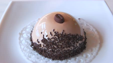 장식 한 : Plate with dome shaped dessert. Cake mirror glaze and chocolate. Decorated coffee mousse cake. New creative design.