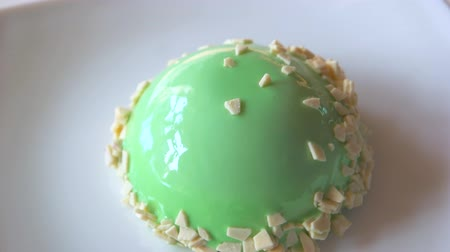 iştah : Yummy dessert with green glaze. Small green cake on plate. Delicious mint mousse cake. Taste of perfection. Stok Video