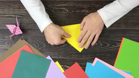 kutilství : Male hands taking yellow paper. Making triangle with origami paper, top view.