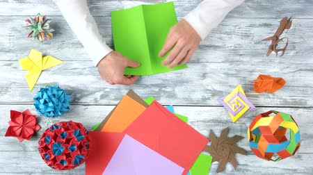 сложить : Torning green paper by hands. Folding colorful paper while making origami figures. Top view, flat lay.