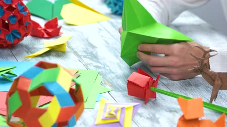 kartka papieru : Origami crafts. Male hands making origami with green paper, close up.