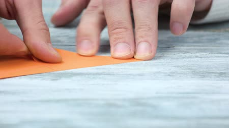 折り紙 : Creating origami, close up. Male hands and orange paper. 動画素材