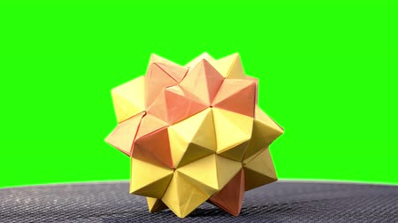 um objeto : Orange origami spiky ball exposition. Green hromakey background for keying.