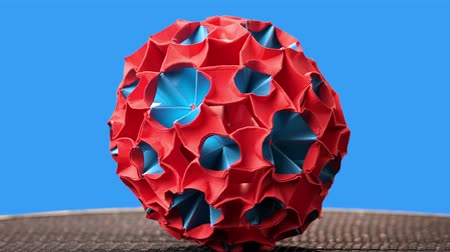 modul : Red and blue origami magic ball model. Sphere rotation. Blue background.