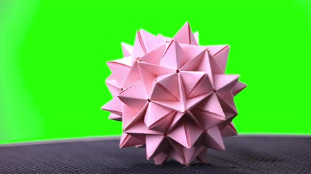 um objeto : Pink origami spiky ball. Green hromakey background for keying.