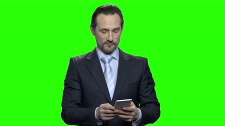 hromakey : Portrait of handsome mature caucasian man using his smartphone. Green screen hromakey background for keying.