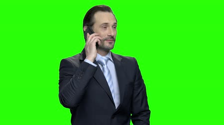hromakey : Handsome mature businessman talking on phone. Middle-aged man in suit. Green screen hromakey background for keying.