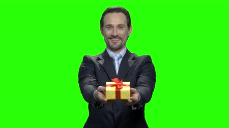 hromakey : Middle aged man in suit giving you gift. Green hromakey background for keying.